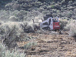 Small front-loader used to clear fire line around private property