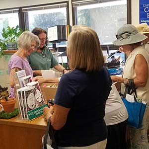 master gardener volunteers talking to clients in the office
