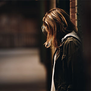 Woman leaning against a wall with her head down