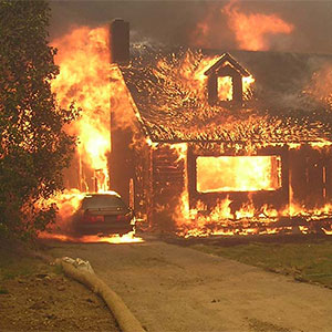 A house and car completely engulfed in flames