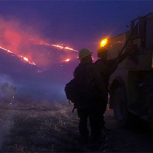 Firefighters with firetruck in the foreground; hillside on fire in the background