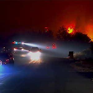 Cars driving at night while a wildfire approaches the road