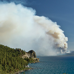 The Angora Fire burns hillsides across Lake Tahoe. Smoke plumes in the air.