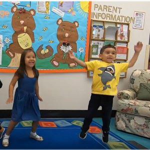 2 kids doing jumping jacks.