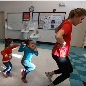 3 kids following the instructor as they jump one one foot around a room.