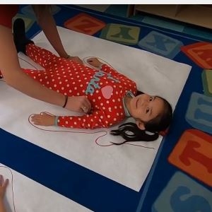 A kid laying on the floor with their body being traced on a piece of paper.