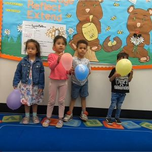 Four kids standing in a line holding balloons.