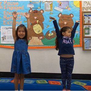 2 girls holding up their arms in the shape of a Y.
