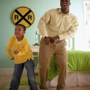 A father and son dancing together in their living room.