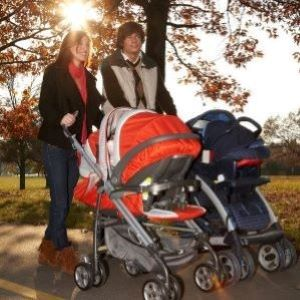 Two parents on a walk pushing strollers.