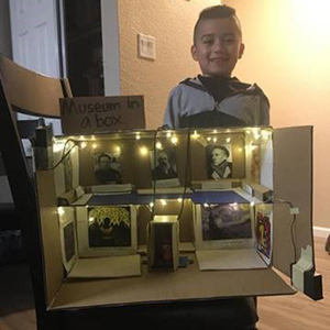 A young child with his family's museum in a box diorama