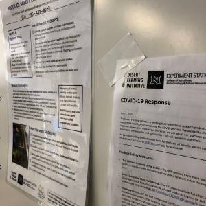 Laminated food safety forms hang on a board in the work space