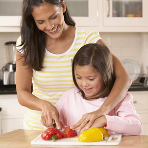 mother slicing fruit with daugher