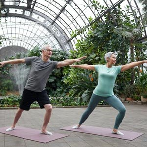 older couple holding a yoga pose together