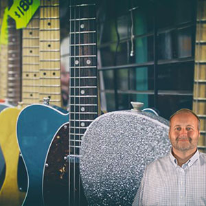 Several guitars of different colors with Mike Bindrup