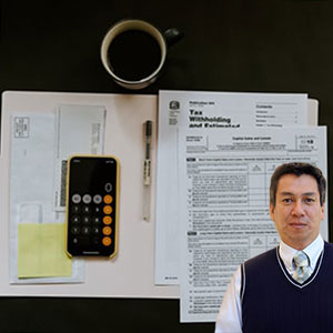 Calculator and tax forms on a desk with Juan Salas