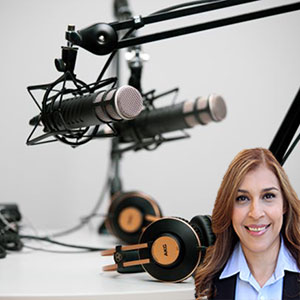 Microphones and headphones on a desk with Reyna Mendez