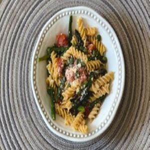A plate of pasta with spring vegetables.