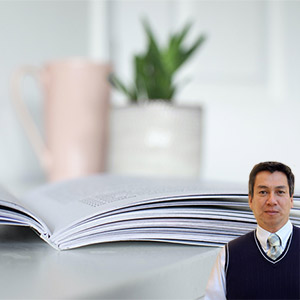 Open book with plant in background with Juan Salas
