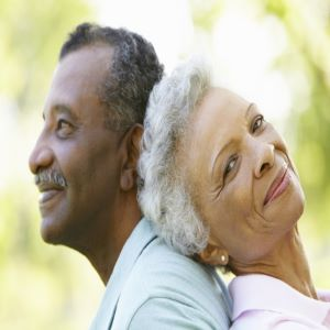 Older adult woman leaning back to back with an older adult man.