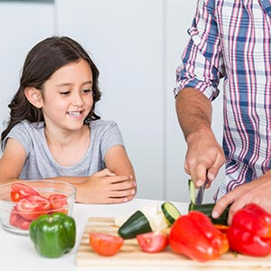 a girl watching her dad slice a vegetable