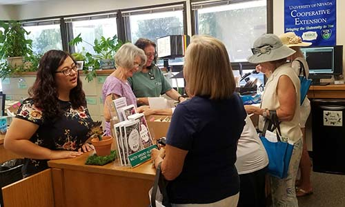 master gardeners answering questions for clients at office desk