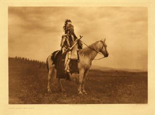 American Indian in traditional clothing astride a horse.