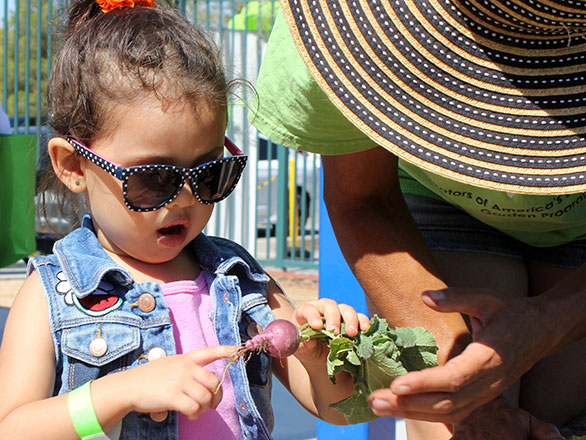 content block size young girl looking excitedly at a freshly picked radish