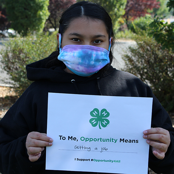 4-H youth holding up a sign that reads 'To me, opportunity means getting a job'