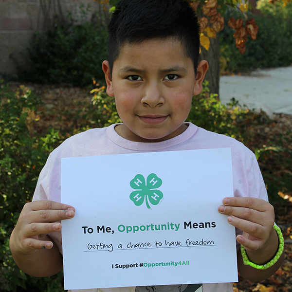 4-H youth holding up a sign that reads 'To me, opportunity means getting a chance to have freedom''
