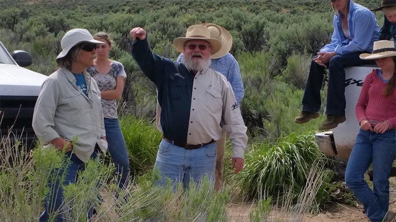 People on a ranch tour discussing rangeland management.