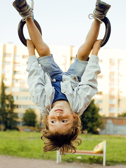 a child hanging upsidedown on playground rings