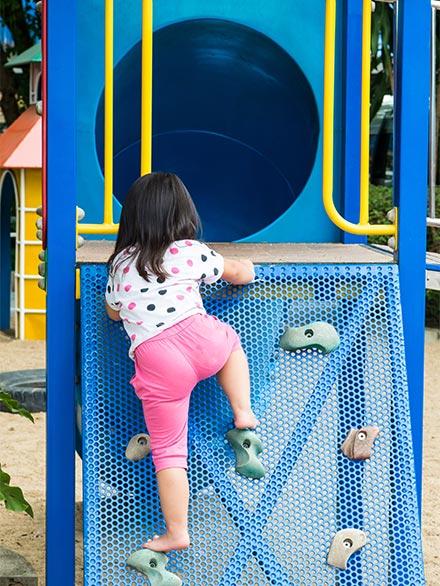 kid climbing up playground equipment