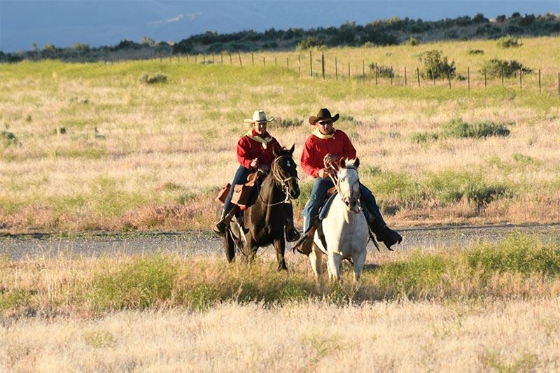 People on horseback riding across rangeland.