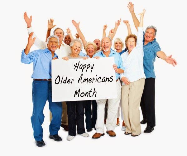 """A group of older adults with their arms up and holding a sign that reads """"Happy Older Americans Month""""."""
