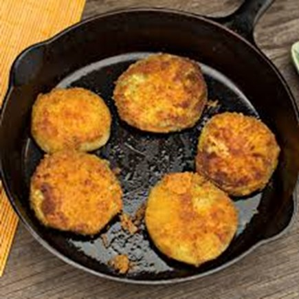 Fried green tomatoes cooking on a hot skillet.