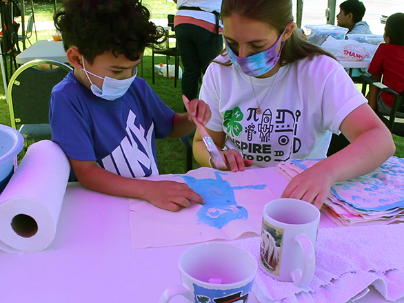 A 4-H youth works with a 4-H leader on a STEM project.