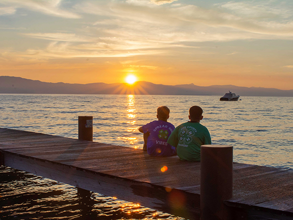 Two 4-H boys watching the sunset on a dock.
