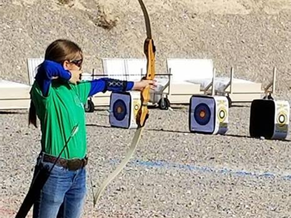 4-H youth shooting a bow and arrow