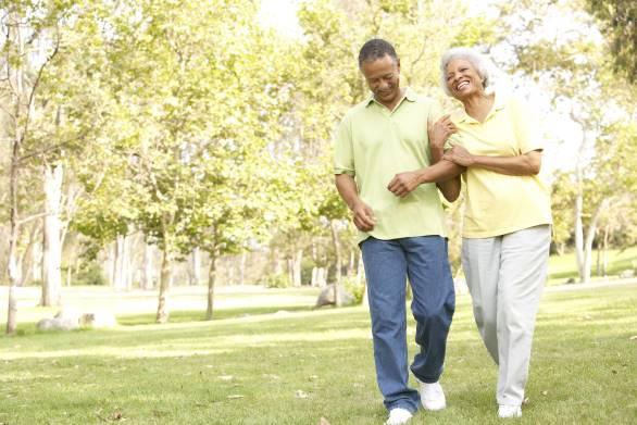Older adult couple walking together through park.