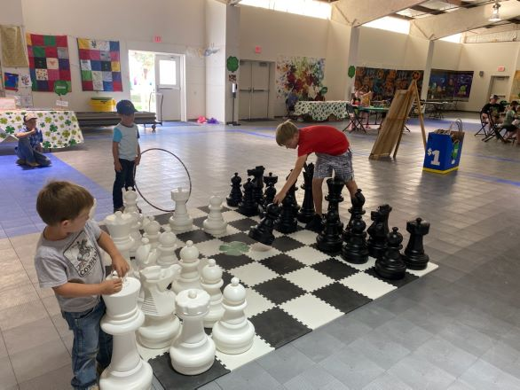 Three young boys play chess on a life-sized chess board.