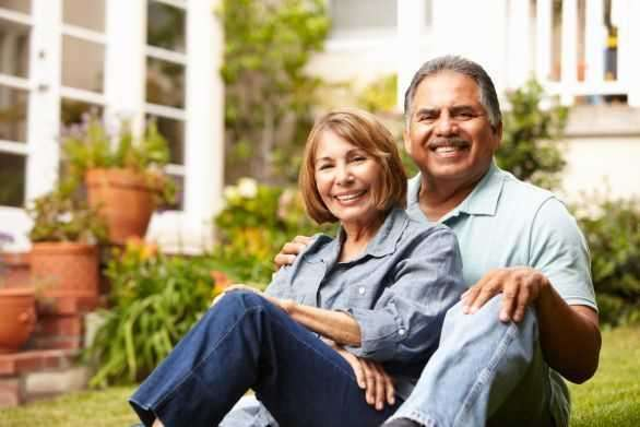 Two older adults sitting in the grass.