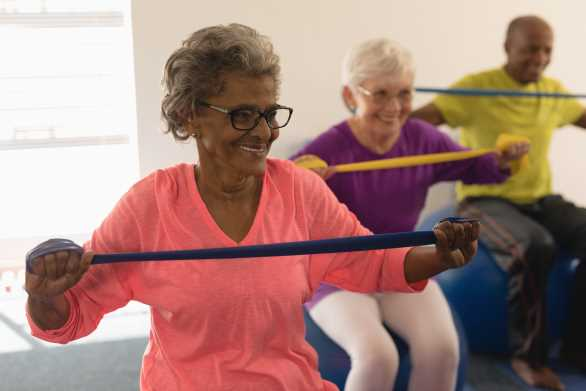 Group of older adults using a resistance band while seated