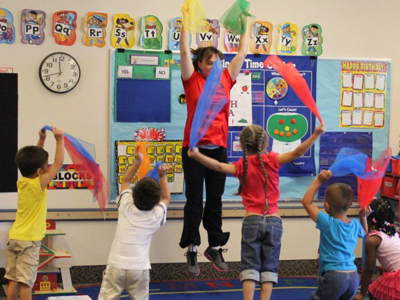 Kids and leader dancing with colored scarves in a classroom