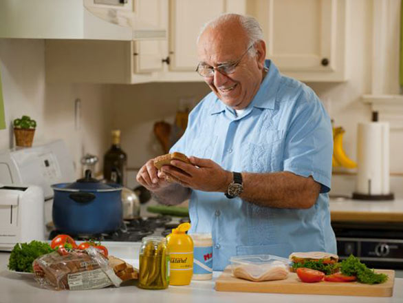 An older adult man prepares a sandwich