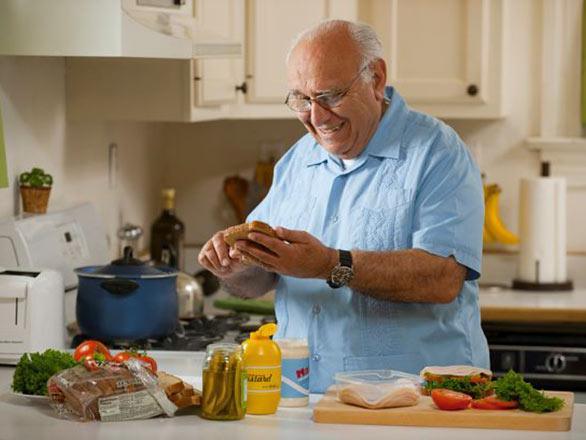 An older adult man prepares a sandwich