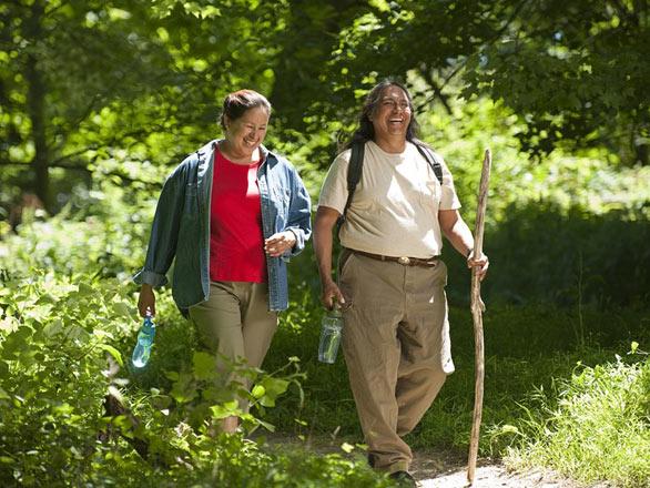 Two adults hike along a walking trail