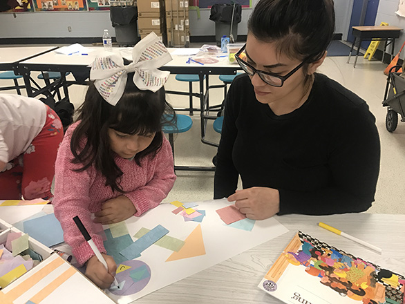 A mother and daughter work together on creating artwork with colored paper shapes at a Let's Discover STEM workshop.