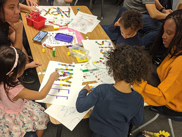 Parents and children doing a name craft at a Fun to Play class