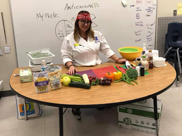 Chef Suzy in front of a white board surrounded by ingredients